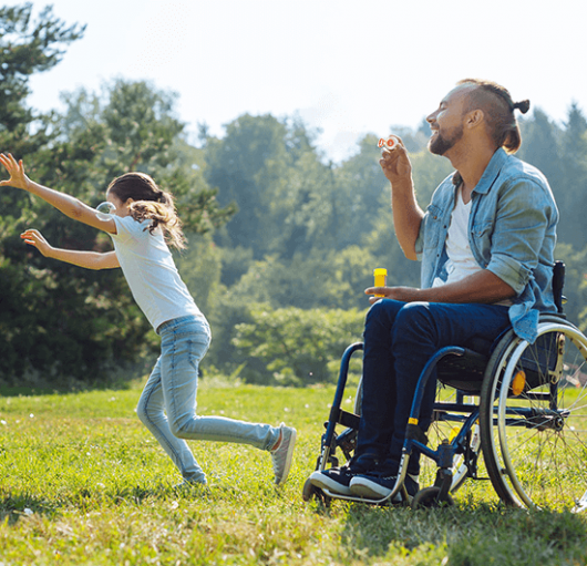 glücklicher Rollstuhlfahrer mit Kind